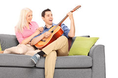 Indivíduo novo que joga a guitarra com sua amiga Imagens de Stock