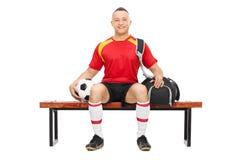 Indivíduo novo que mantém o futebol assentado em um banco Fotografia de Stock Royalty Free