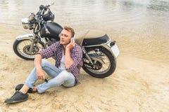 Indivíduo novo que senta-se ao lado de sua motocicleta do vintage Fotografia de Stock