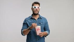 Indivíduo novo que veste um par dos vidros 3D que comem a pipoca e o riso video estoque