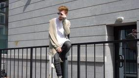 Indivíduo ocasional com a roupa boa que senta-se em uns trilhos na rua vídeos de arquivo