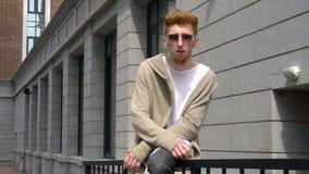 Indivíduo ocasional com a roupa boa que senta-se em uns trilhos na rua video estoque
