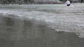 Indivíduo que anda na areia ao longo da costa da borda do ` s da água vídeos de arquivo