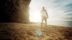 Indivíduo que anda na praia na manhã As ondas grandes deixam de funcionar e quebram Silhueta do surfista fêmea com a prancha no s filme