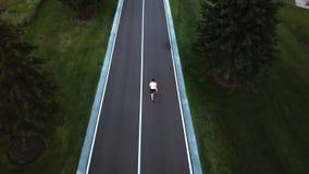 Indivíduo que corre ao longo da estrada, vista traseira video estoque