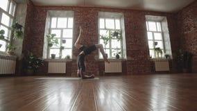 Indivíduo que faz a ioga dentro perto das janelas Ioga praticando do homem novo no estúdio vídeos de arquivo