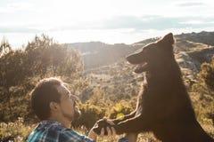 Indivíduo que joga com seu cão no por do sol foto de stock