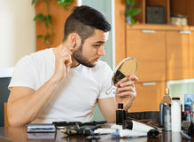 Indivíduo que remove o cabelo da orelha Imagens de Stock