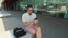 Indivíduo que senta-se com smartphone fora filme
