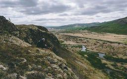 Indivíduo que senta-se na borda de um penhasco em Islândia fotos de stock