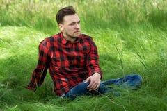 Indivíduo que senta-se na grama Foto de Stock
