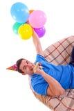 Indivíduo que senta-se no sofá com um tampão e balões e assobio imagens de stock