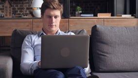 Indivíduo que senta-se no sofá no plano vídeos de arquivo