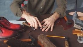 Indivíduo que trabalha com couro usando-se crafting a ferramenta na oficina vídeos de arquivo