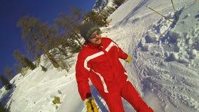 Indivíduo que vai abaixo da inclinação no dia claro que toma o vídeo do selfie, esporte de inverno extremo vídeos de arquivo