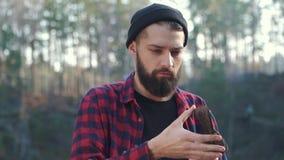Indivíduo sério brutal com machado fora Estada farpada do homem com um machado em sua mão na floresta video estoque
