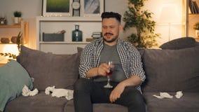 Indivíduo sensível que grita guardando o vidro do vinho usando o smartphone que senta-se em casa