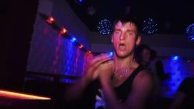 Indivíduo suado em uma dança do t-shirt em um clube noturno em filme