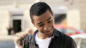 Indivíduo tímido de sorriso considerável que fala em seu smartphone filme