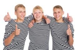 Indivíduos de sorriso com polegares aumentados Fotografia de Stock Royalty Free