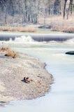 Indivíduos dos amigos que sentam-se pela cachoeira pequena do inverno do rio Fotos de Stock Royalty Free