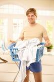 Indivíduo de sorriso com cesta de lavanderia Imagem de Stock
