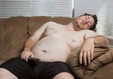 Indivíduo gordo preguiçoso que olha a tevê Imagem de Stock Royalty Free