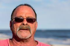Indivíduo idoso na praia com óculos de sol Fotografia de Stock Royalty Free