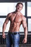 Indivíduo 'sexy' novo muscular que levanta nas calças de brim e desencapado-chested Imagens de Stock Royalty Free