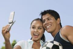 Individu de couples photographiant avec le téléphone portable Photo stock