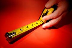 Individu rétractant l'outil de mesure de bande chez la main de la femme Image stock