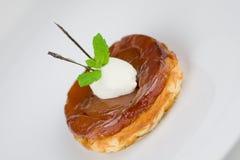 Individual apple tart Tatin. Upside down apple tart Tatin, classic french dessert.  Finished with Chantilly cream, mint and caramelised(edible) vanilla pod Royalty Free Stock Photos