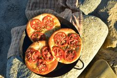 Individual baked tomato foccacia bread. Individual serving size baked focaccia bread on rocky seashore in Baja Mexico Royalty Free Stock Photos