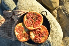 Individual baked tomato foccacia bread. Individual serving size baked focaccia bread on rocky seashore in Baja Mexico Stock Photos