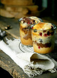 Individual cake desserts in glasses. With a fruity variety with berries and a chocolate and vanilla marbled cake cooling on a wire rack on a burlap cloth in a stock images