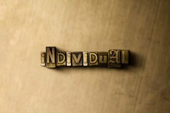 INDIVIDUAL - close-up of grungy vintage typeset word on metal backdrop Royalty Free Stock Image