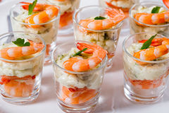Individual Cocktail Shrimp Shooters with delicious homemade aiol. I spicy sauce decorated with parsley leaf on white platter for festive dinner or cocktail party Stock Photo