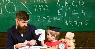 Individual education concept. Lesson in the classroom. Young teacher and little kid sitting at the desk. Excited boy royalty free stock photography