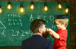 Individual education concept. Little boy playing with beard of man next to him. Adult turned back and smiling child in royalty free stock photos