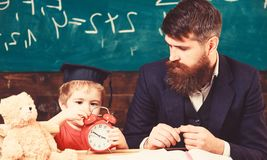 Individual education concept. Teacher and pupil in the classroom. Little boy learning the time. Cute kid in graduation royalty free stock photography