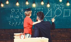 Individual education concept. Teacher and schoolboy turned back in classroom. Kid in graduation cap holding adult male stock photo