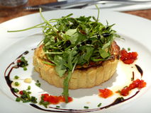 Individual goats cheese tart and rocket leaves. Individual goats cheese tart on a white plate with a rocket leaf salad, drizzled with balsamic vinegar stock photography