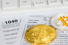Tax return form 1040 with bitcoin and litecoin. Individual income tax return form 1040 with bitcoin and litecoin metallic coins, tax and credits section stock photography