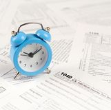 1040 Individual income tax return form and blue alarm clock. 1040 Individual income tax return form with blue alarm clock. Concept of tax period in United States royalty free stock images