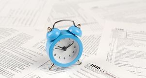 1040 Individual income tax return form and blue alarm clock. 1040 Individual income tax return form with blue alarm clock. Concept of tax period in United States stock images