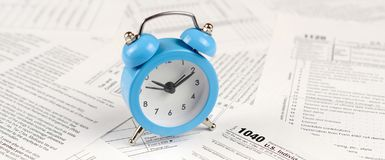 1040 Individual income tax return form and blue alarm clock. 1040 Individual income tax return form with blue alarm clock. Concept of tax period in United States stock photography