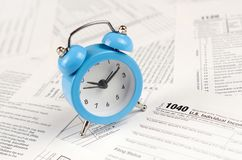 1040 Individual income tax return form and blue alarm clock. 1040 Individual income tax return form with blue alarm clock. Concept of tax period in United States stock image