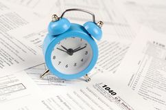 1040 Individual income tax return form and blue alarm clock. 1040 Individual income tax return form with blue alarm clock. Concept of tax period in United States stock photos