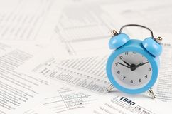 1040 Individual income tax return form and blue alarm clock. 1040 Individual income tax return form with blue alarm clock. Concept of tax period in United States royalty free stock image