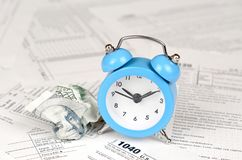 1040 Individual income tax return form with blue alarm clock and crumpled hundred dollar bill. Concept of tax period in United States stock photo